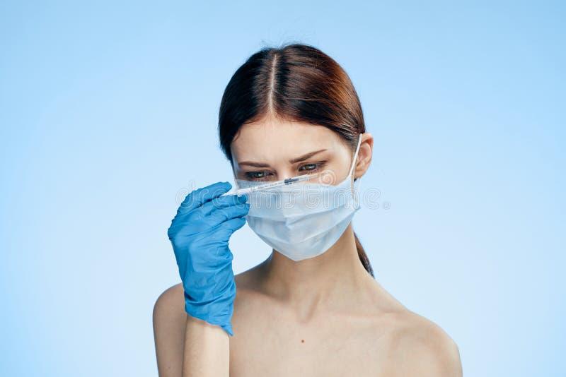 Den unga härliga kvinnan på en blå bakgrund i en medicinsk maskering och bärande handskar rymmer en injektionsspruta, medicin, pl arkivfoton