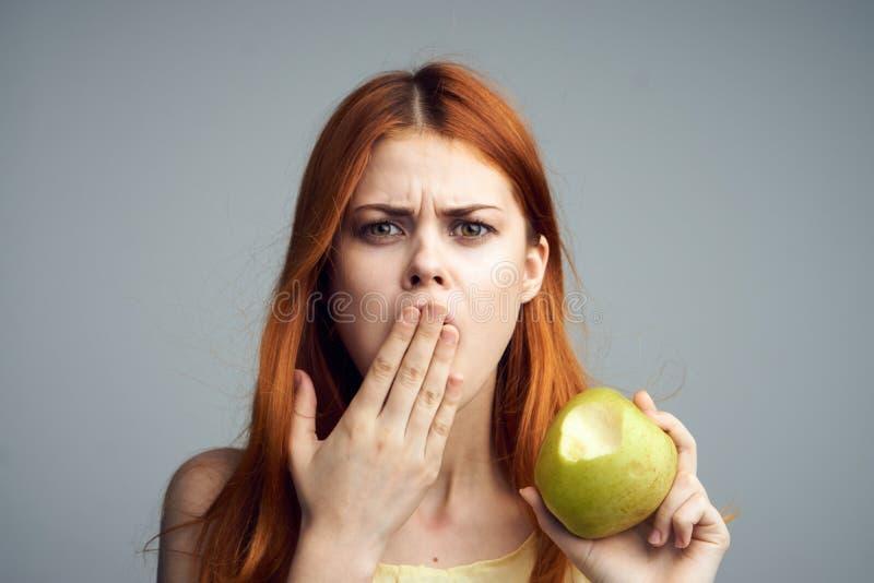 Den unga härliga kvinnan på en grå bakgrund rymmer ett äpple, smärtar i tänder, bantar arkivbilder