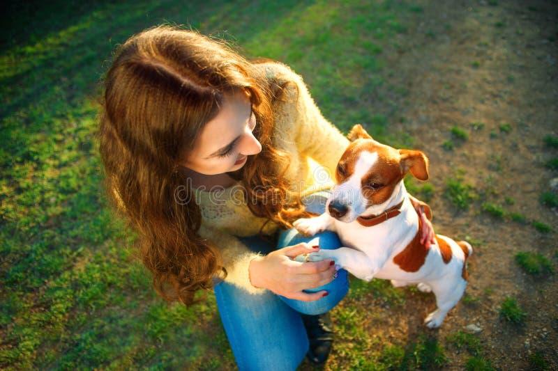 Den unga härliga kvinnan rymmer en hand över den älsklings- hunden som ` s tafsar på en bakgrund av våren parkerar arkivfoto