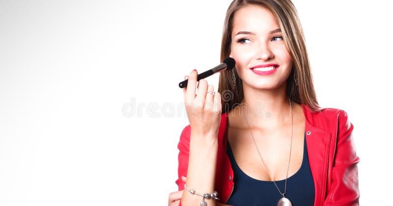 Den unga härliga kvinnan rymmer i handborsten för makeup arkivfoto