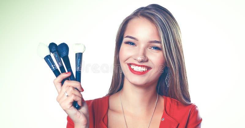Den unga härliga kvinnan rymmer i handborsten för makeup arkivfoton
