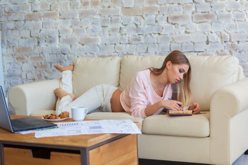 Den unga härliga kvinnan sitter på en soffa på en vit bakgrund för tegelstenvägg med en kopp kaffe Bärbar dator dokument royaltyfria bilder