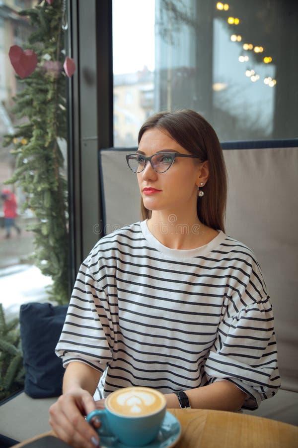 Den unga härliga kvinnan sitter på tabellen i kafédrinkkaffe väntar på begrepp för bra morgon för businesspartner royaltyfri bild