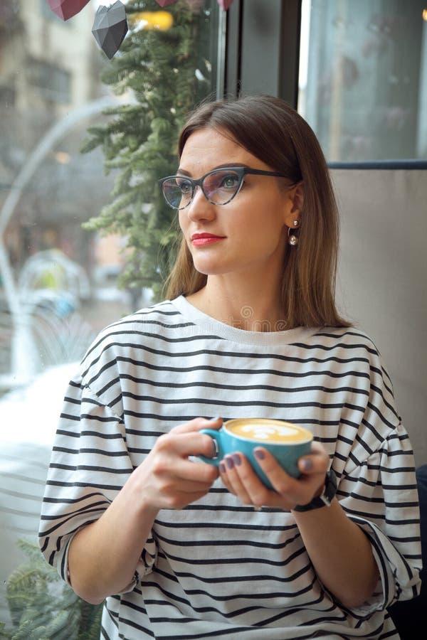 Den unga härliga kvinnan sitter på tabellen i kafédrinkkaffe väntar på begrepp för bra morgon för businesspartner royaltyfria bilder