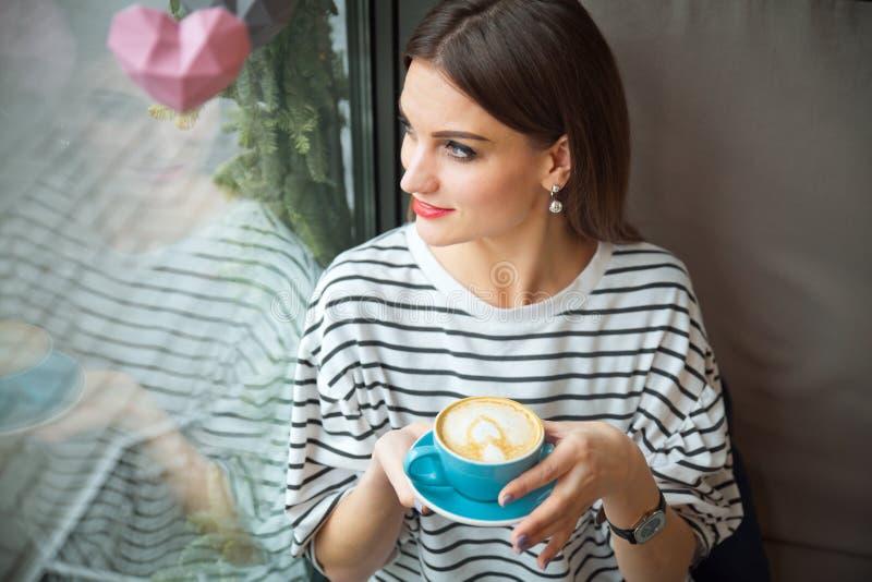 Den unga härliga kvinnan sitter på tabellen i kafédrinkkaffe väntar på begrepp för bra morgon för businesspartner arkivfoto