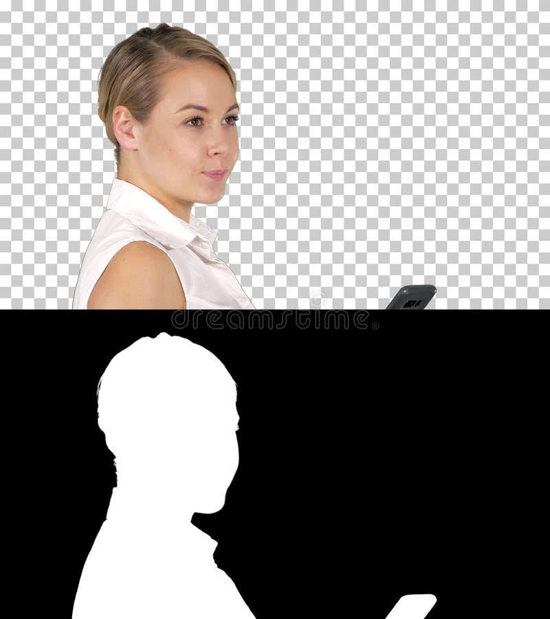 Den unga härliga kvinnan skriver en SMS, Alpha Channel royaltyfri bild