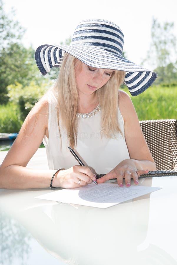 Den unga härliga kvinnan skriver på sheed av papper royaltyfri fotografi