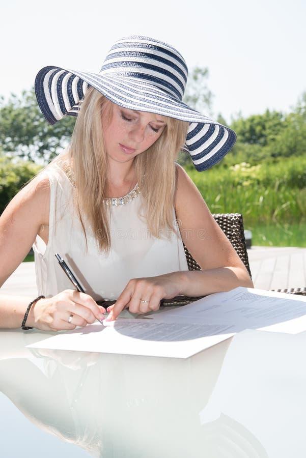 Den unga härliga kvinnan skriver på sheed av papper fotografering för bildbyråer