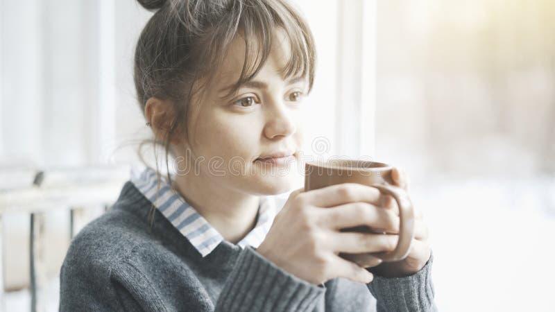 Den unga härliga kvinnan som bär en grå tröja, tycker om hennes te i ett kafé och dagdrömma royaltyfria bilder