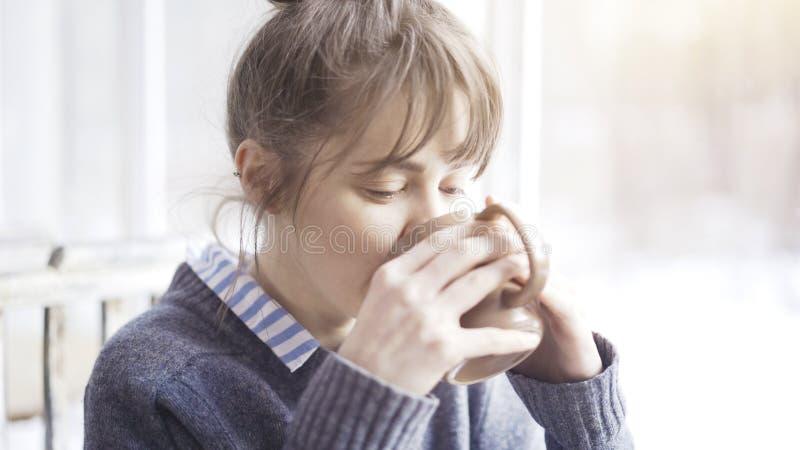 Den unga härliga kvinnan som bär en grå tröja, tycker om hennes te i ett kafé och dagdrömma royaltyfri bild