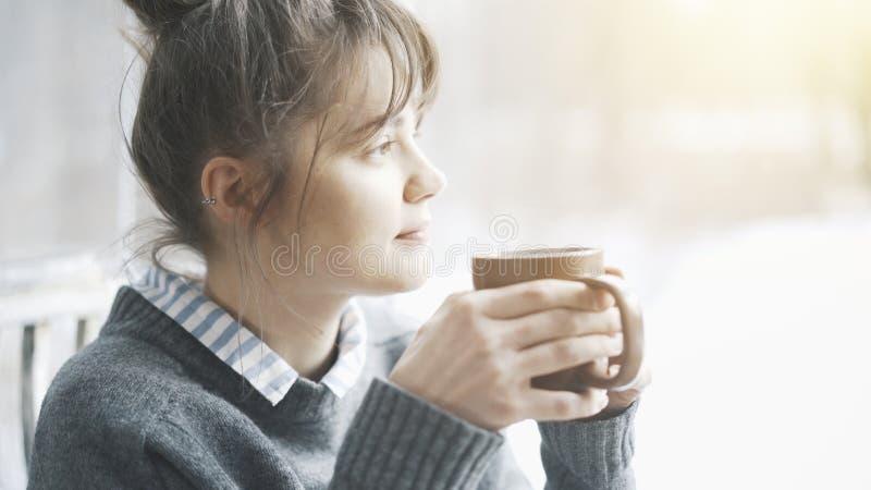Den unga härliga kvinnan som bär en grå tröja, tycker om hennes te i ett kafé och dagdrömma royaltyfria foton