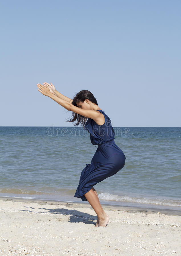 Den unga härliga kvinnan som gör yoga på sjösidan i blått, klär royaltyfri bild
