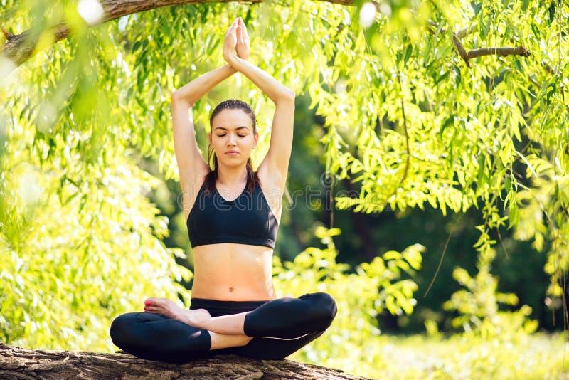 Den unga härliga kvinnan som utomhus sitter i en yogaposition, i, parkerar, skogmeditationen Lotus Position arkivfoton