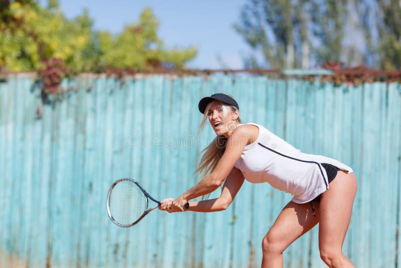 Den unga härliga kvinnan spelar tennis Oavkortad tillväxt royaltyfri bild