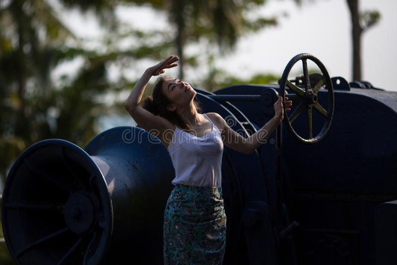 Den unga härliga kvinnan står på den jätte- motorn av ett övergett skepp royaltyfria foton