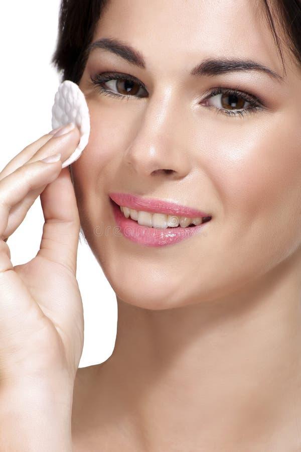 Den unga härliga kvinnan tar bort makeup från perfekt hud arkivfoto