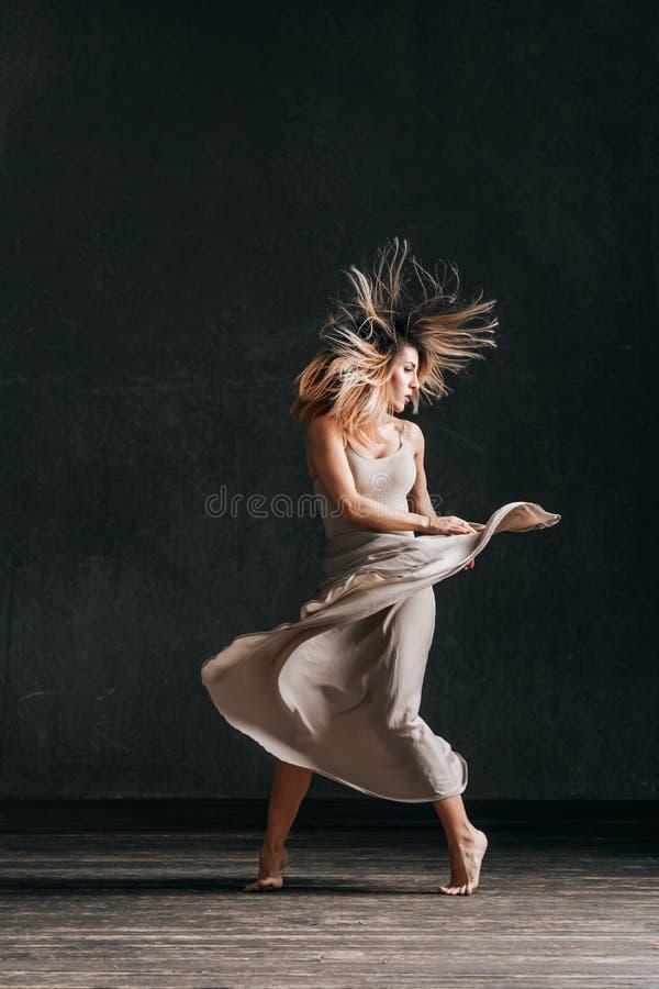Den unga härliga kvinnliga dansaren poserar i studion royaltyfri foto