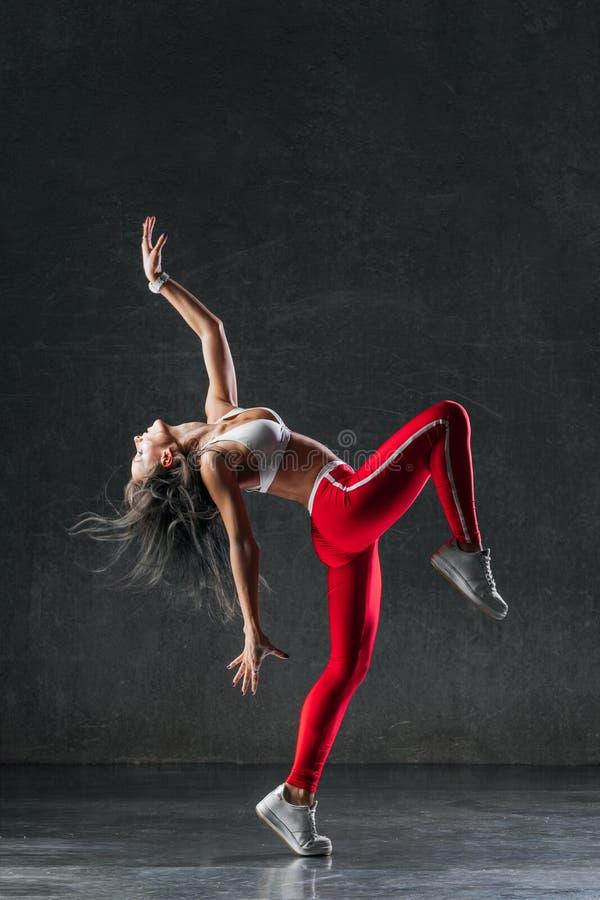 Den unga härliga kvinnliga dansaren poserar i studion arkivbild