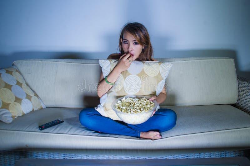 Den unga härliga latinska kvinnan koncentrerade fullständigt hållande ögonen på intensiv film på natten som äter popcorn som sent arkivbild