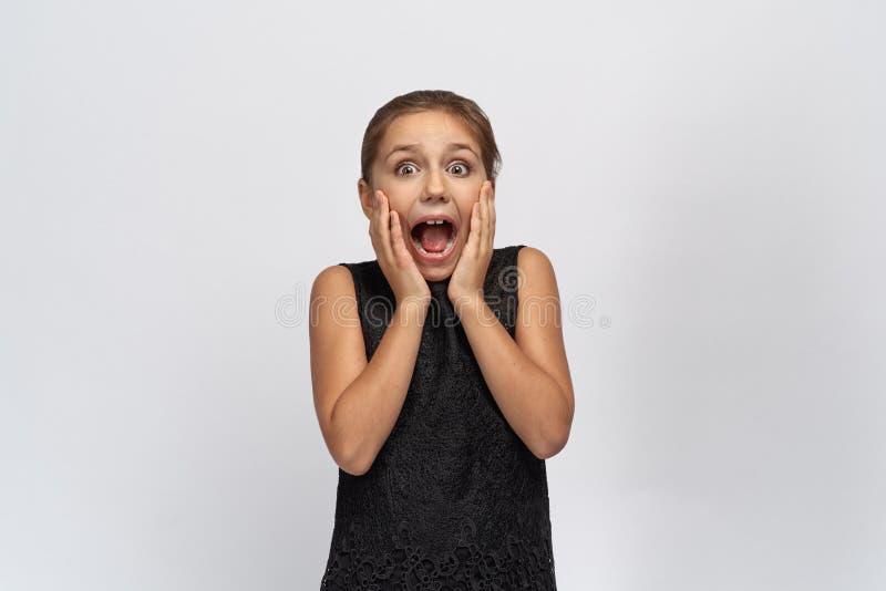 Den unga härliga lilla flickan täcker hennes mun i chock, ser känslomässigt med stor överraskning på kameran, öppnar brett ögon arkivfoton