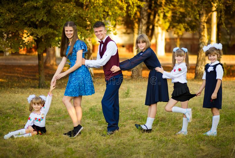 Den unga härliga modern leder fem barn till skola Moder av många barn stor familj lyckligt tillsammans royaltyfria foton