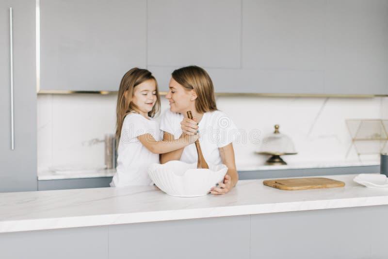 Den unga härliga modern med hennes lilla dotter lagar mat royaltyfri bild