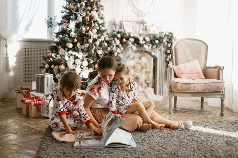 Den unga härliga modern med två lilla döttrar sitter på mattan och läste boken nära det nya årets träd med gåvor in arkivbilder