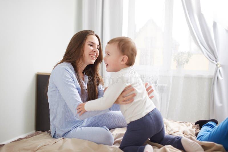 Den unga härliga modern och hennes iklädda pyjamas för liten son har gyckel på sängen i det ljusa hemtrevliga sovrummet royaltyfria bilder