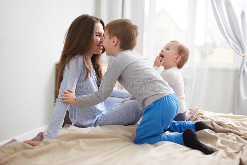 Den unga härliga modern och hennes två iklädda pyjamas för små söner har gyckel på sängen i det ljusa hemtrevliga sovrummet royaltyfri bild