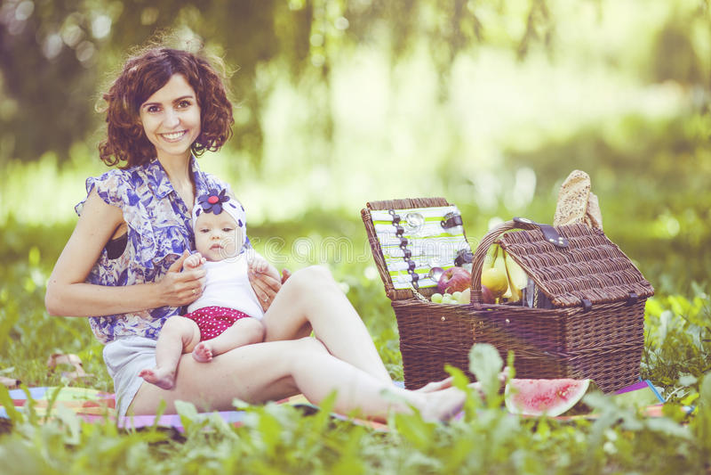 Den unga härliga modern sitter med hennes dotter på filten parkerar in arkivfoton