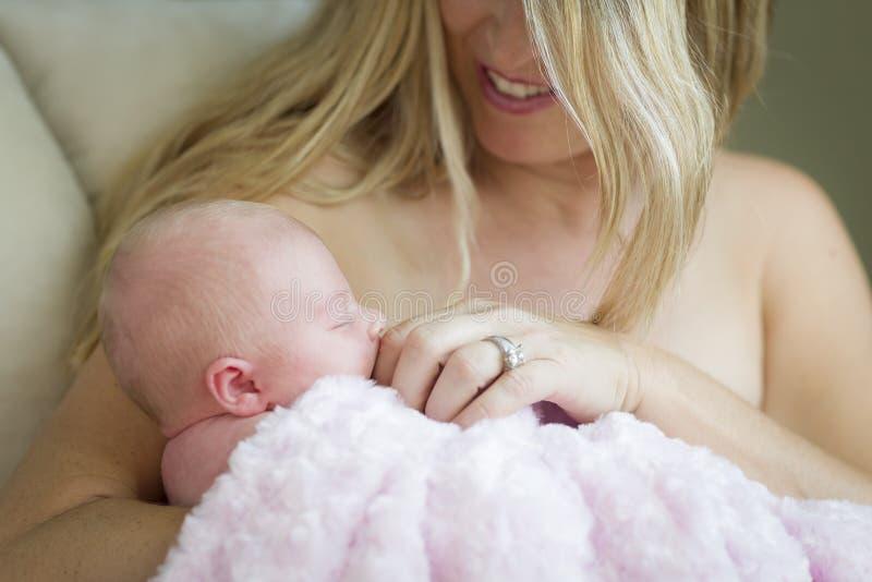 Den unga härliga modern som rymmer hennes dyrbara nyfött, behandla som ett barn flickan fotografering för bildbyråer