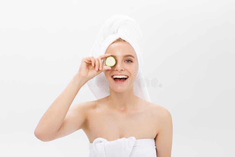 Den unga härliga näcka flickan som ler nederlag, synar bak gurkaskivor över vit bakgrund Skönhetskincare och royaltyfria foton