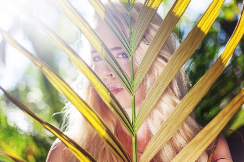 Den unga h?rliga sinnliga flickan p? bakgrunden av en tropisk tr?dg?rd, ser till och med ett blad av g?mma i handflatan arkivbilder