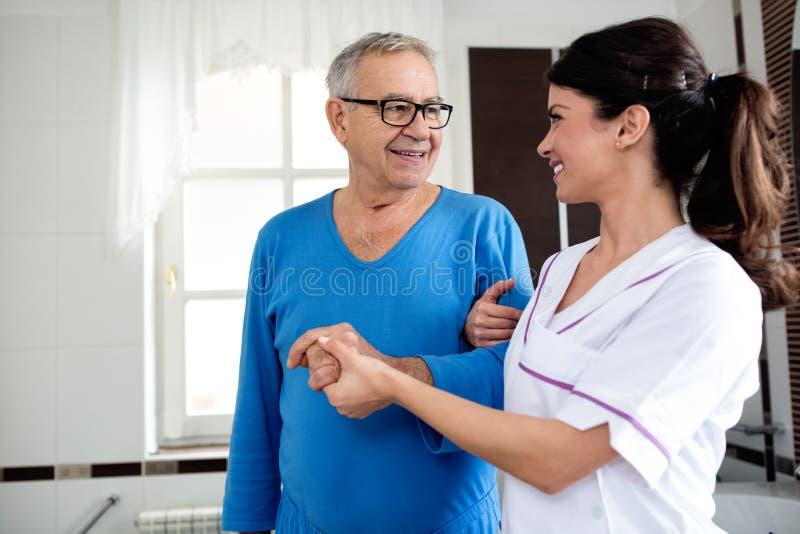 Den unga härliga sjuksköterskan hjälper till den höga mannen på badrummet arkivfoton