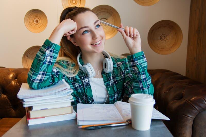 Den unga härliga studentflickan gör hennes läxa eller förbereder sig till examina som placerar med bokförskriftsböcker arkivbild