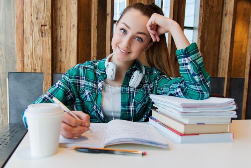 Den unga härliga studentflickan gör hennes läxa eller förbereder sig till examina som placerar med bokförskriftsböcker fotografering för bildbyråer