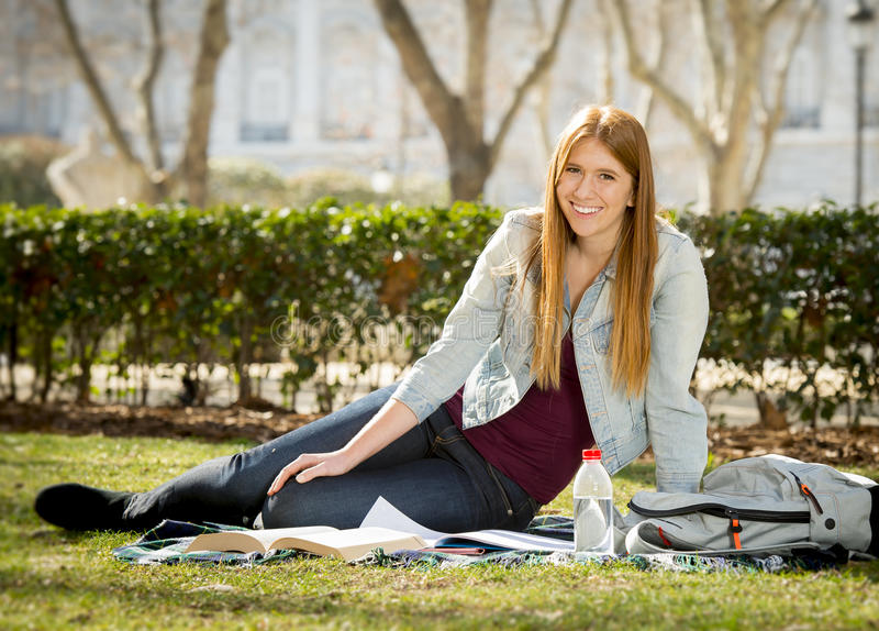 Den unga härliga studentflickan på universitetsområde parkerar gräs med böcker som studerar lycklig förberedande examen i utbildn royaltyfria foton