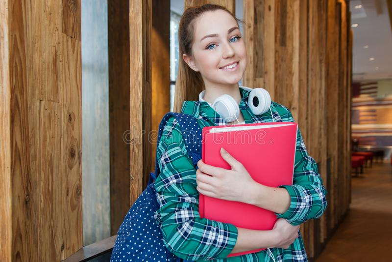 Den unga härliga studentflickan står med ryggsäcken och rymmer mappen i hennes händer royaltyfri fotografi