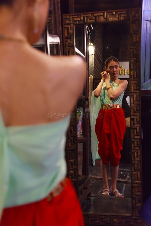 Den unga härliga thailändska asiatiska kvinnadressingen i retro traditionell thailändsk dräkt för tappning klär upp framme av spe royaltyfria foton