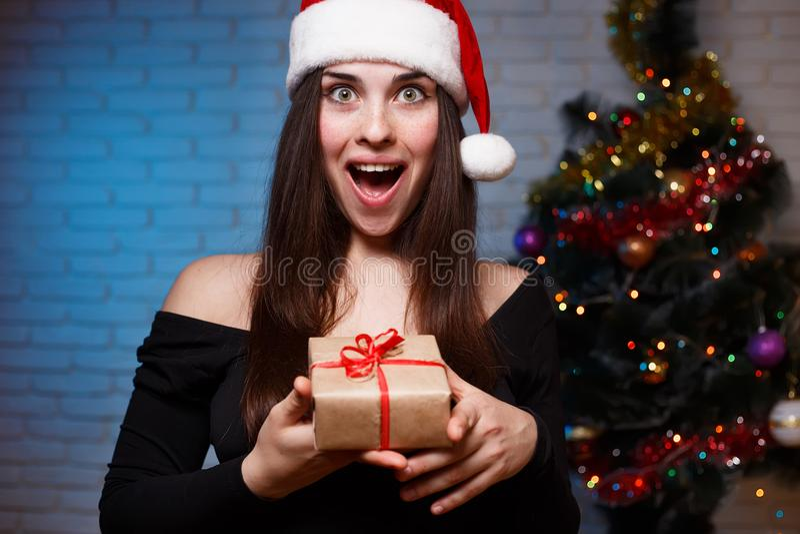 Den unga härliga upphetsade kvinnan i aftonklänning och jultomten cap hol royaltyfria foton