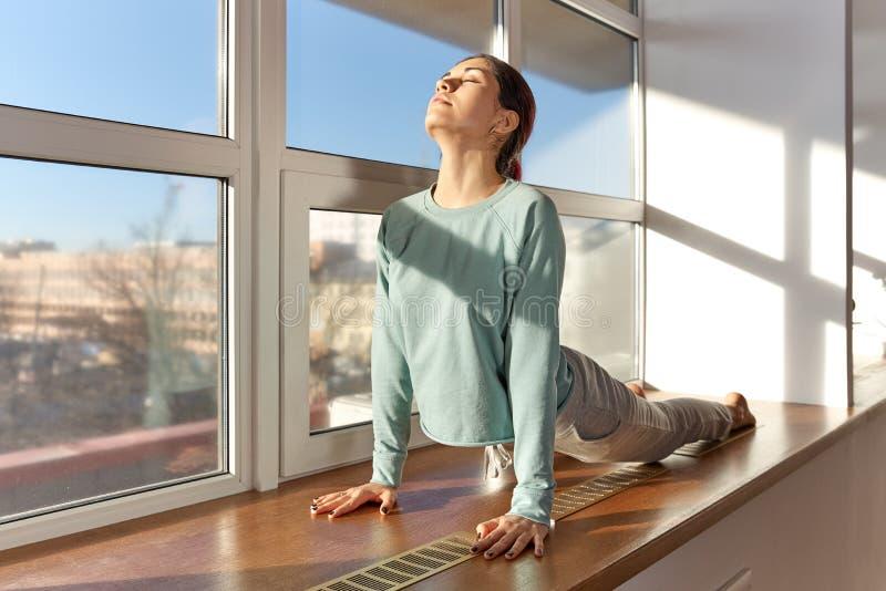 Den unga härliga vit-flådde kvinnan som gör yogaövningar, sträcker arkivfoto