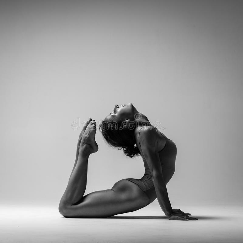 Den unga härliga yogakvinnan poserar i studio svart white arkivfoton
