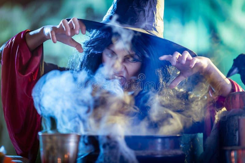 Den unga häxan lagar mat med magi royaltyfria bilder