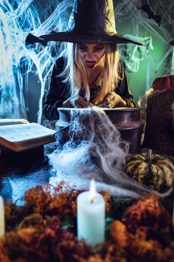 Den unga häxan lagar mat med magiska ben royaltyfri fotografi