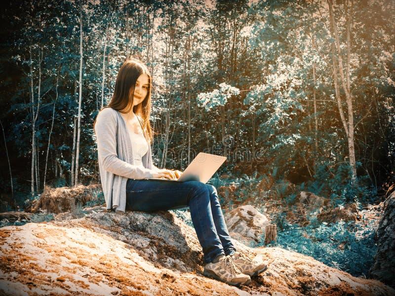 Den unga h?rliga flickan arbetar p? en b?rbar dator, medan sitta p? ett stort, vaggar i det frilans- begreppet f?r skogen royaltyfria bilder
