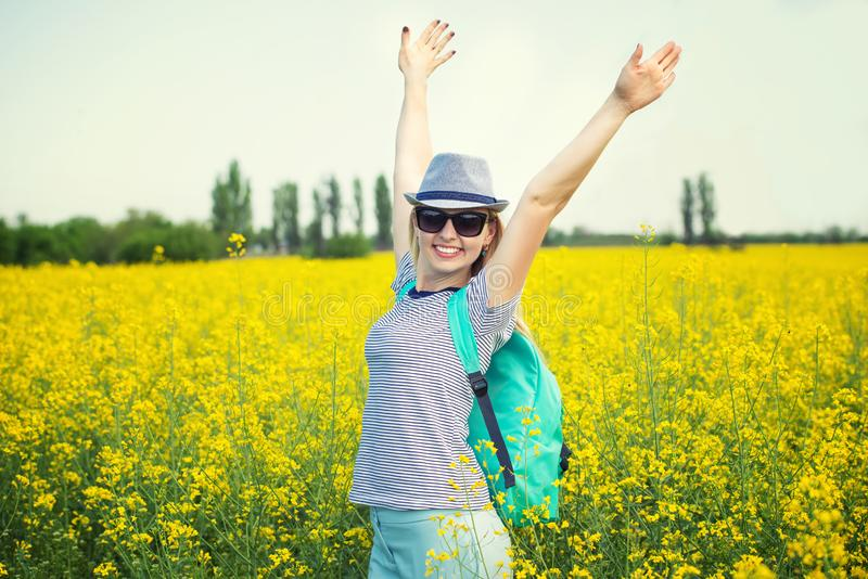 Den unga h?rliga kvinnan promenerar ett blomma f?lt p? en solig dag royaltyfria bilder