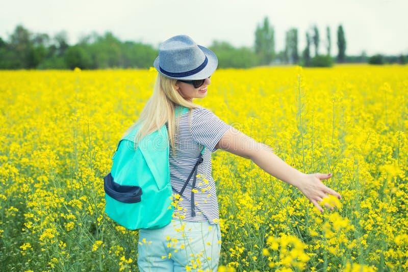 Den unga h?rliga kvinnan promenerar ett blomma f?lt p? en solig dag fotografering för bildbyråer
