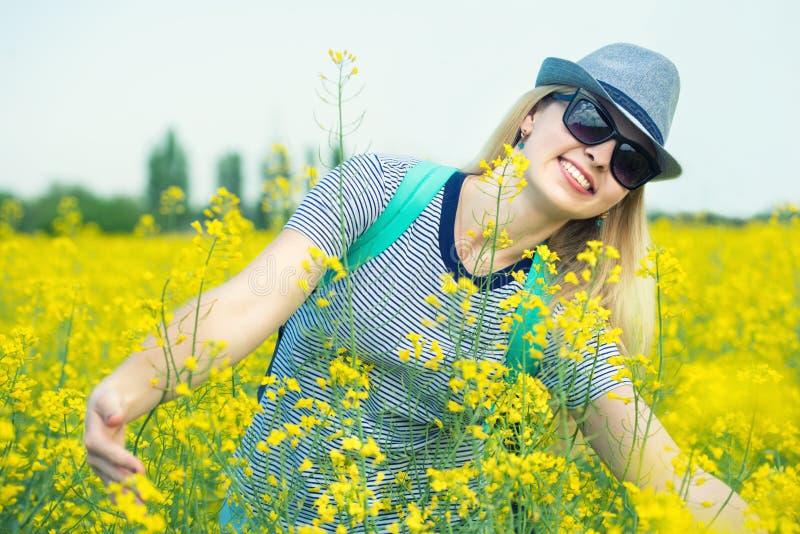 Den unga h?rliga kvinnan promenerar ett blomma f?lt p? en solig dag arkivfoto