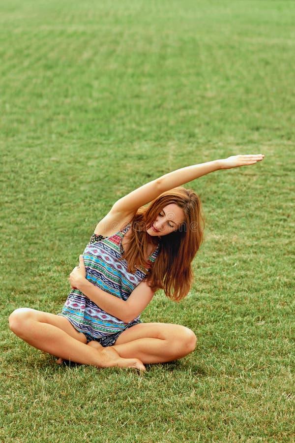 Den unga h?rliga kvinnan ?va yoga p? Sunny Meadow aktiv livsstil Skönhetkvinna som gör sund yoga och yogabegrepp Fitn royaltyfria foton