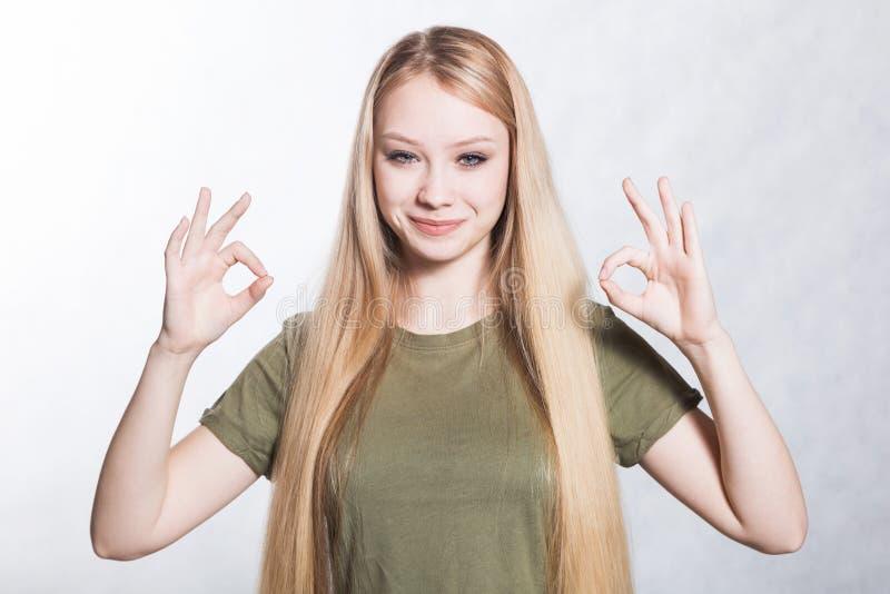 Den unga h?rliga le kvinnan visar det ok tecknet Kroppsspr?kbegrepp arkivfoto